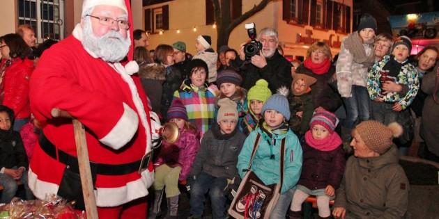Aus der Dunkelheit kam der Nikolaus und bahnte sich den Weg zur großen Kinderschar am großen Weihnachtsbaum vor dem Rathaus. Foto: Hannelore Nowacki