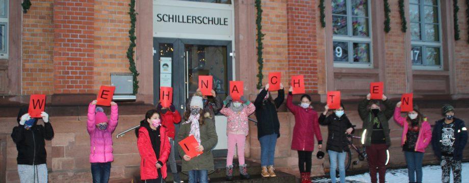 Der erste Schnee fällt und das erste Adventskalendertürchen der Schillerschule öffnet sich. Mit einem kleinen Beitrag zum Auftakt sorgte die Klasse 4a für besinnliche Weihnachtsstimmung. Foto: Eva Wiegand