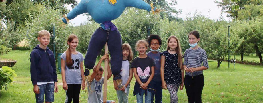 Spaß beim kreativen Arbeiten hatten die Ferienkinder beim Obst- und Gartenbauverein. Die eindrucksvolle Strohpuppe hat das Potenzial Besucher willkommen zu heißen oder als Vogelscheuche zu wirken. Foto: Hannelore Nowacki