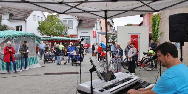 Auf dem Wochenmarkt herrschte am Samstagvormittag reges Treiben auch bei Sprühregen. Viele Besucher zog es zu Matthias Karb, der als Sänger am Keyboard ein buntes Wunschkonzert bot. Foto: Hannelore Nowacki