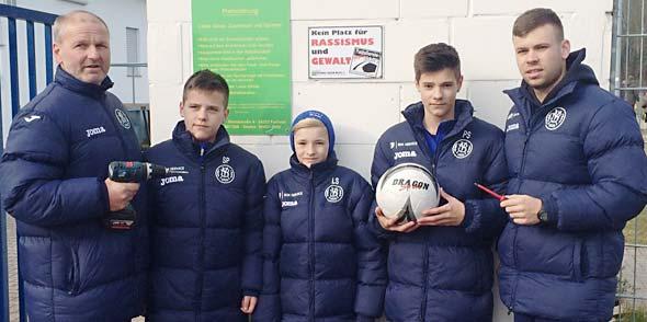 Das Foto zeigt den 1. SVH-Vorsitzendehn Wilfried Adelfinger (links), den SVH-Jugend-Koordinator Yannick Bog (rechts) und einige der SVH-Nachwuchs-Kicker.
