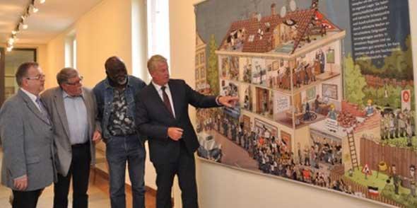 """OB Michael Kissel zeigt verschiedenen Tafeln der Ausstellung """"Neofaschismus in Deutschland"""" mit authentischen Szenen neofaschistischer Aktivitäten."""