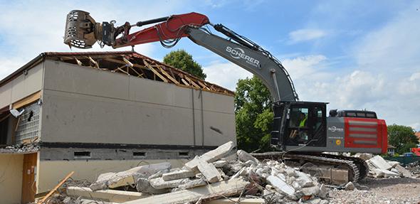 Ein gewaltiger Bagger machte sich am Dienstagnachmittag an den Abriss der alten Sporthalle in Pfeddersheim. Foto: Gernot Kirch