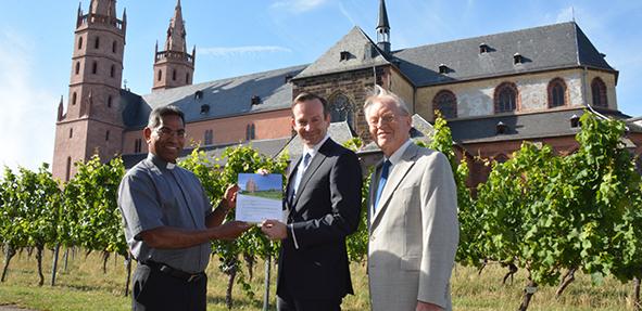 Die Übergabe der Rebstockpatenschaft. Von links: Pfarrer Dr. George Ambadan, Dr. Volker Wissing und Harald Unselt. Foto: Gernot Kirch