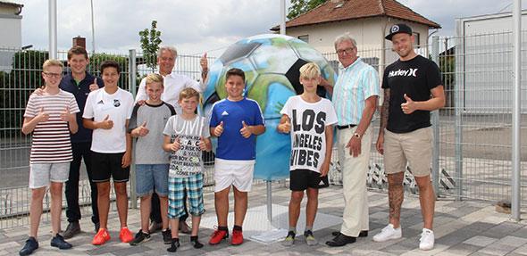 """Freuen sich über das fertige Fußball-Kunstwerk: die Gimbsheimer Jugendspieler, """"Anpfiff ins Leben""""-Koordinator Nico Marquardt (2. von links), Unterstützer Frank Dinter (Ressortleiter Vertrieb der EWR, 5. von links), """"Anpfiff ins Leben""""-Chef Dietmar Pfähler (2. von rechts) und Graffiti-Künstler Daniel Ferino (rechts außen)."""