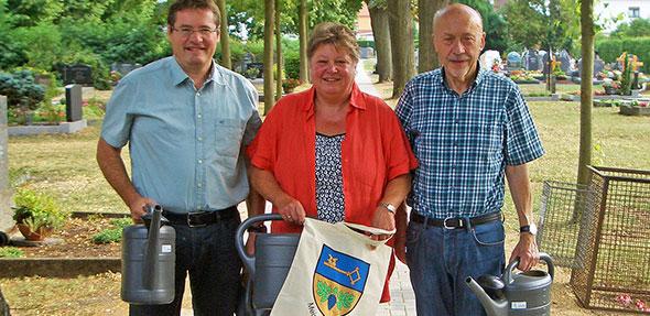Peter Karlin, Brigitte Geiser und Peter Brandau (von links) loben den Ausbau des Friedhofs-Hauptwegs und spenden im Rahmen ihrer Ortsbegehung zehn Gießkannen.