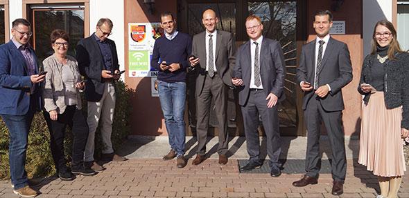 Freuen sich über das schnelle und öffentliche WLAN-Netz am VG-Verwaltungsgebäude in Eich und testen das neue Angebot: Heike Reuper, SPD (2.v.l.), VG-Chef Maximilian Abstein (4.v.l.) und Thorsten Volz von der EWR AG (5.v.l.).