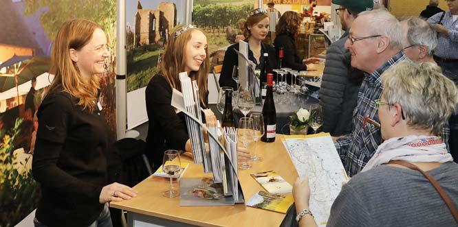 Bereits freitags bestand großes Interesse am Messestand des Landkreises. Elfi Theiß (Wirtschaftsförderung Alzey-Worms) und Anja Dehos (VG Wöllstein) hatten in der Beratung alle Hände voll zu tun. Am ersten Messetag unterstützten die Weinmajestäten der VG Wöllstein mit einem Weinausschank. Foto: WfG Alzey-Worms/Alexander Sell