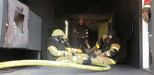 Die Feuerwehrleute während der Trainingsrunde im Inneren des Brandcontainers. Foto: Evonik