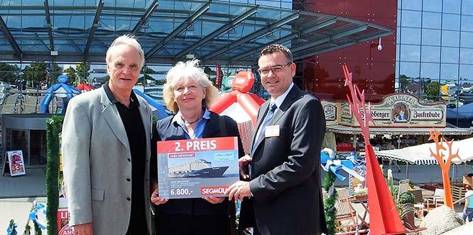 Nahmen ihren Gewinnpreis vor dem Einrichtungshaus von Segmüller entgegen: Helmut und Doris Bürschgens aus Gießen, zusammen mit Sascha Kaminski, Geschäftsleiter von Segmüller in Weiterstadt.