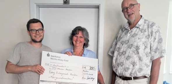 SPD-Vorsitzender Kevin Zakostelny übergibt den Spendenscheck an MGH-Koordinatorin Sabine Bayer und Pfarrer Volker Hudel (von links).