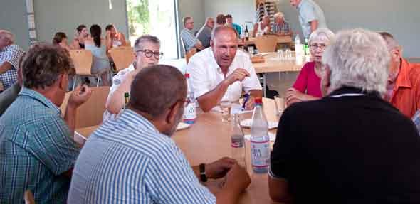 Adolf Kessel (weißes Hemd) hört zu in Ibersheim. An voll besetzten, großen Tischgruppen saßen die Besucher.Viele von ihnen brachten Themen vor, die ihnen in Ibersheim wichtig sind.