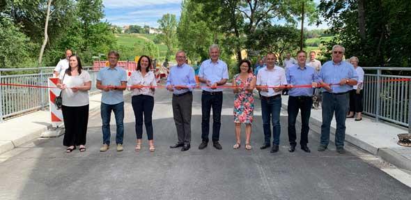 Landrat Ernst Walter Görisch und der Leitende Baudirektor Bernhard Knoop (LBM Worms) geben gemeinsam mit Vertreterinnen und Vertreter des Landes, Kreises und der Kommunen die neue Pfrimmbrücke für den Verkehr frei.