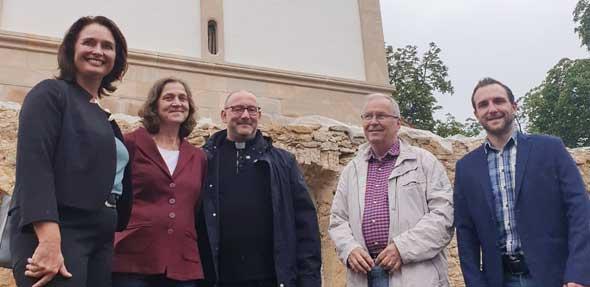 MdL Kathrin Anklam-Trapp gemeinsam mit Ortsbürgermeisterin Jutta Schick, Pfarrer Heiko Heyer sowie den Beigeordneten Rudolf Feile und Tobias Perlick vor der Basilika in Bechtheim.