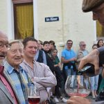 """Von links: Für Altbürgermeister Erno Straus forderte Stephan Huppert in seiner Rolle als """"Jean"""" während der offiziellen Eröffnung Applaus – und natürlich einen vollmundigen Rotwein. Foto: Florian Helfert"""