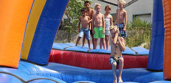 """Die Kinder hatten an der pyramidenähnlichen Wasserhüpfburg """"Tarzan"""", bei der man mit einer Liane auf die andere Seite schwingen muss, sichtlich viel Spaß."""