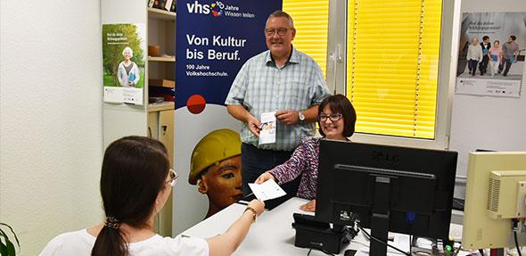 Beraterin Sarah Mühleck übergibt im Beisein von Bildungsdezernent Waldemar Herder einen Prämiengutschein.