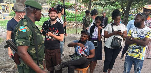 Regisseur Sansi erklärt bewaffneten Soldaten seine Szene.