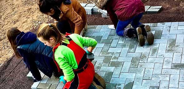 Viele fleißige Schüler pflasterten einen Teil des Schulgartens und verlegten ihr erstes Fischgrätenmuster.