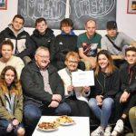"""Spendenübergabe im """"Wohnzimmer"""": Die Jugendlichen aus dem Nordend freuen sich über die Unterstützung der AWF. Dezernent Waldemar Herder und Annelie Büssow (sitzend, Mitte) freuen sich mit ihnen."""