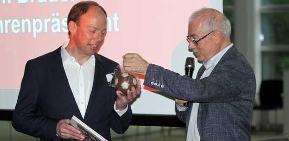 Helmut Emler, vom Wirtschafts – und Verwaltungsrat, bedankte sich noch einmal beim Ehrenpräsidenten Tim Brauer für die geleistete Arbeit für die Wormatia, mit einem Schokoball und einem Fotobuch über die Jahre als Vorsitzender. Foto: Marcus Diehl