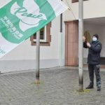 OB Adolf Kessel (links) und Engelbert Kloos hissen die Flaggen als Zeichen des Einsatzes gegen Atomwaffen.