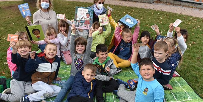 """Sichtbar zeigen die Kinder des """"Kindertreffs 93"""" ihre Freude über die mitgebrachten Bücher im Beisein ihrer Erzieherinnen. Quelle: Stadt Worms"""
